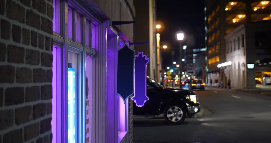 A night establishing shot of a city's bar, cafe, or tattoo parlor with purple neon signs in the window as traffic passes. Blank signs for customization. Additional rights may be needed for commercial    Shutterstock HD Video #1008095461