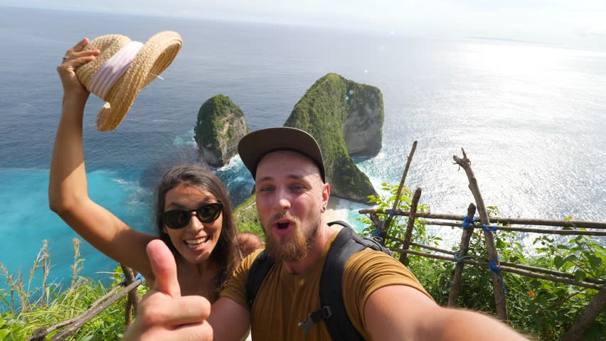Young Mixed Race Tourist Couple Making Funny Selfie Video Chat with Amazing Kelingking Beach on Background. Nusa Penida, Indonesia. 4K. #1008097504