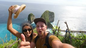 Young Mixed Race Tourist Couple Making Funny Selfie Video Chat with Amazing Kelingking Beach on Background. Nusa Penida, Indonesia. 4K.