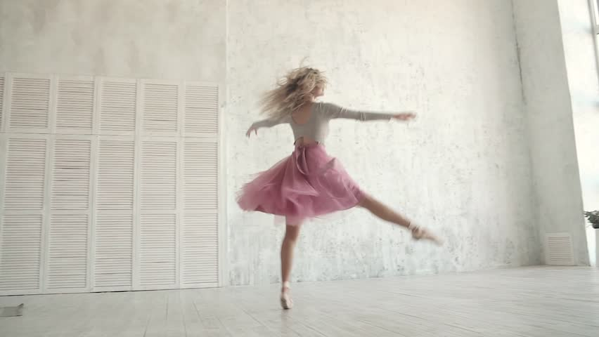 Ballet dancer is spinning and jumping high in a tutu and pointe shoes. young ballerina is dancing. slow motion