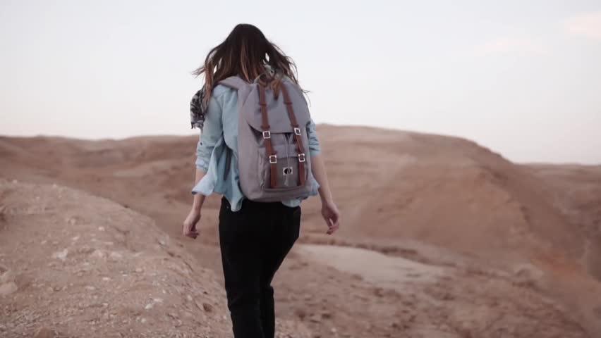 Woman walks near desert canyon. Slow motion. Young woman wanders near sheer drop edge. Rocks and stones. Israel. Freedom | Shutterstock HD Video #1008116866