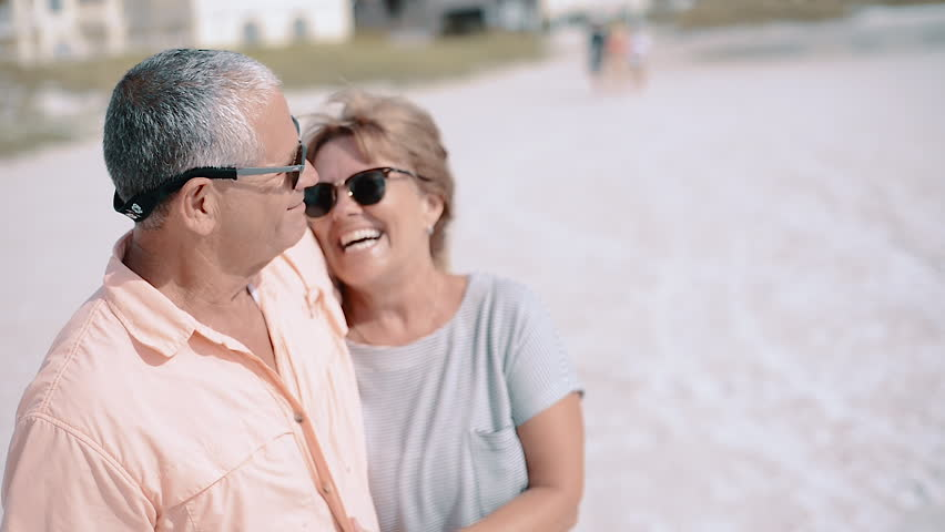 Happy Middle-Aged Couple Laughing, Kissing at the Beach