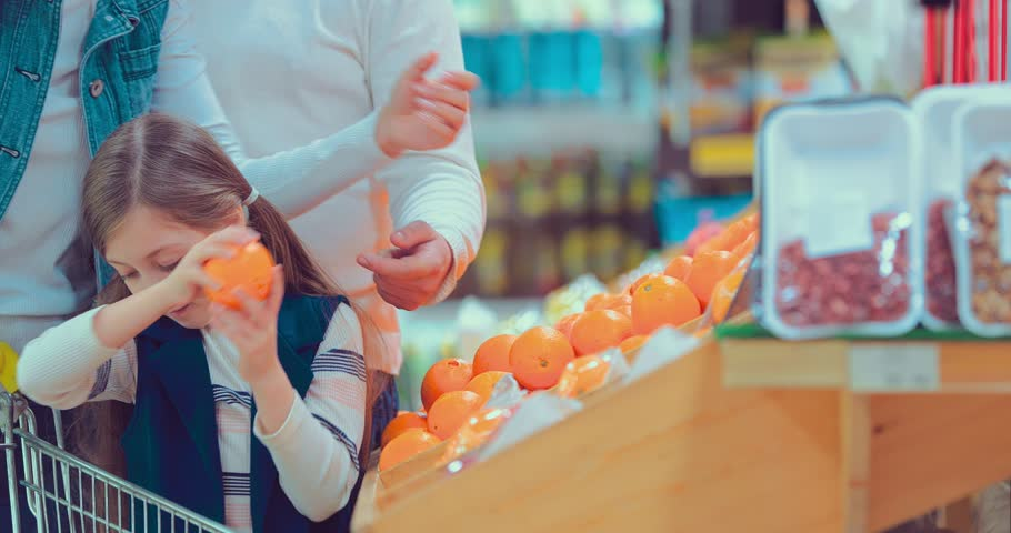Little girl choosing orange at fruit vegetable supermarket #1008145663
