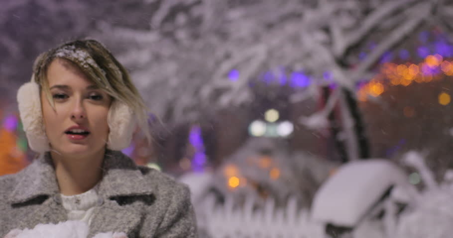 Portrait of beautiful happy girl blowing snow in night winter city, woman looking at camera.  #1008154918