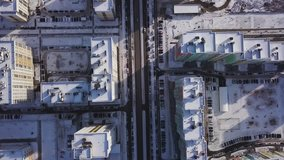 Aerial view snow-covered road with cars in winter. Clip. Aerial view on city in winter day. City panorama with straight road covered with snow from a bird eye view. Winter city streets from a bird eye