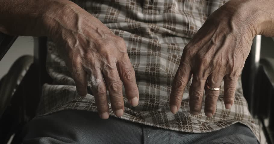Closeup of old man hands with wrinkled skin and looks shaking on the wheelchair at home. Parkinson disease concept shot in 4k resolution