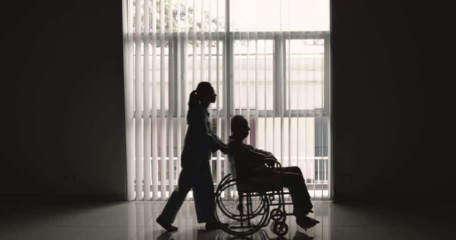 Silhouette of elderly man sitting on wheelchair and pushed by his nurse near the window at home. Shot in 4k resolution | Shutterstock HD Video #1008184723