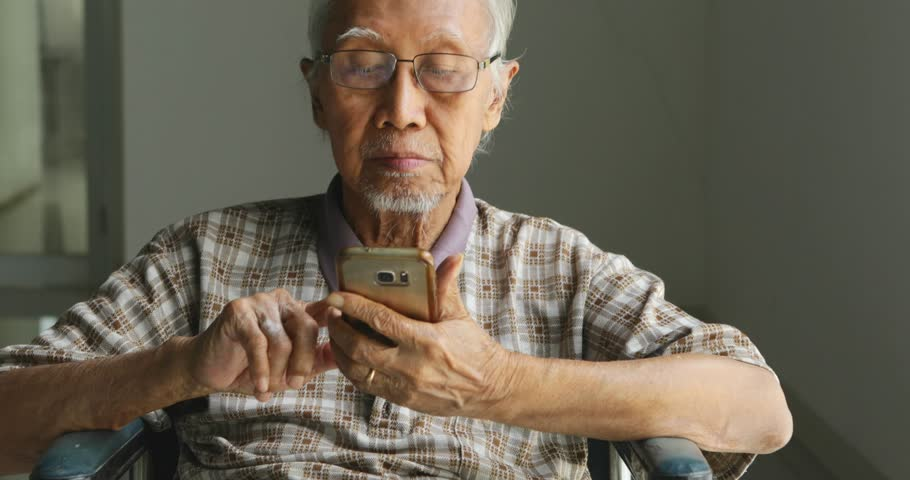 Old man sitting on wheelchair while using a smartphone at home. Shot in 4k resolution