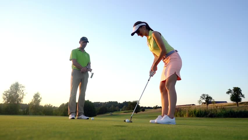 Full length side view of a female golf player ready to hit the ball into the cup under the guidance of a qualified instructor during class outdoors at a modern country club