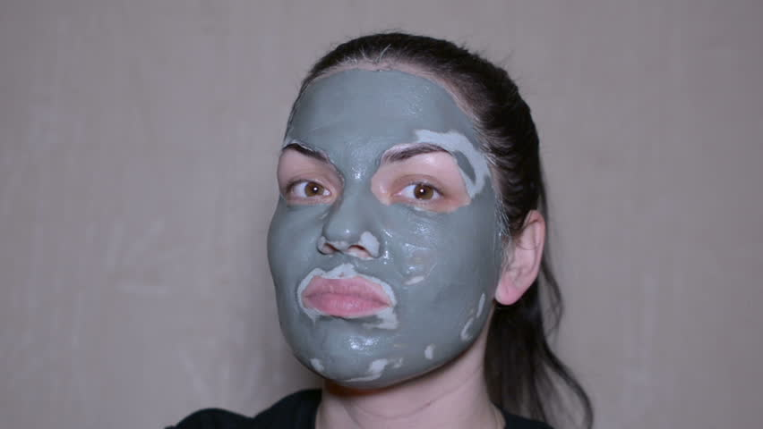 Girl with a clay mask on emotional face