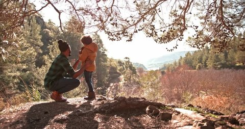 Hipster father and son having fun together standing on mountain peak and looking at view