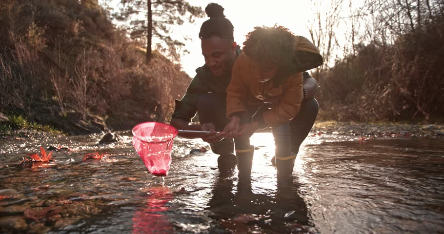 Hipster father and young son catching fish together with fishing net in mountain river stream