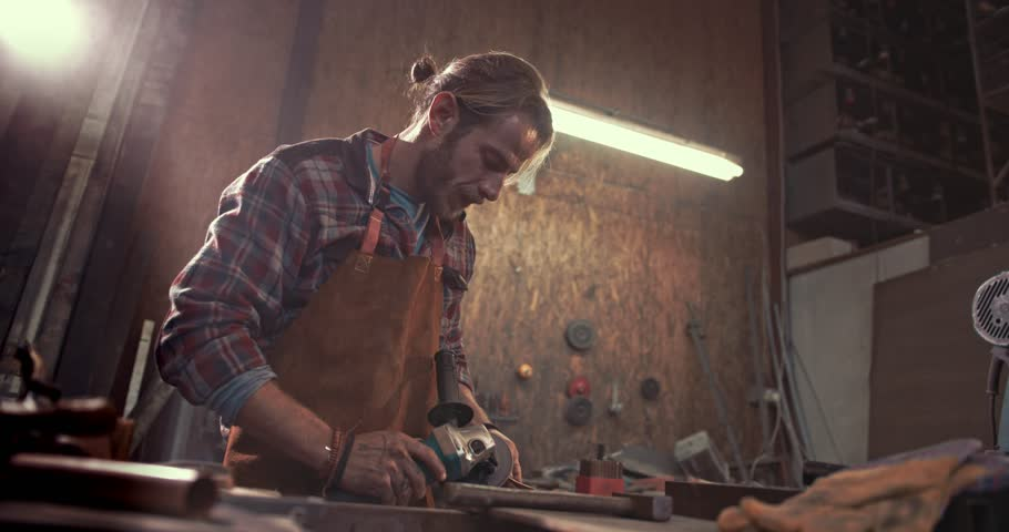 Craftsman using sand paper power tool and polishing metal in industrial factory workshop