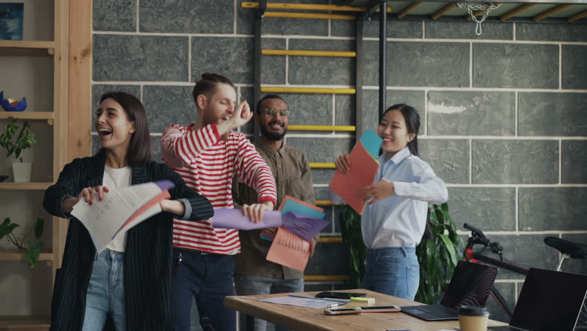 Diverse group female and male start-up business team have fun dancing party in modern office throwing paper documents and celebrating success of project #1008210976