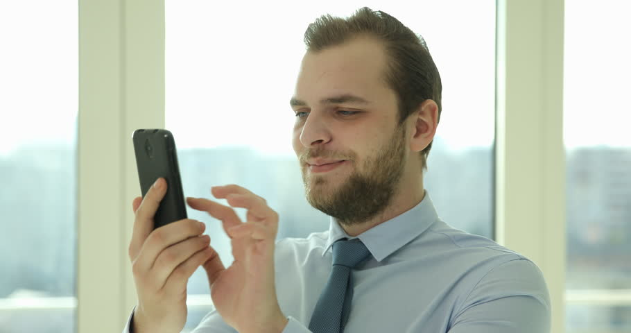 Happy Business Man Using Mobile Phone Sending Email to Partner Office Activity #1008215650