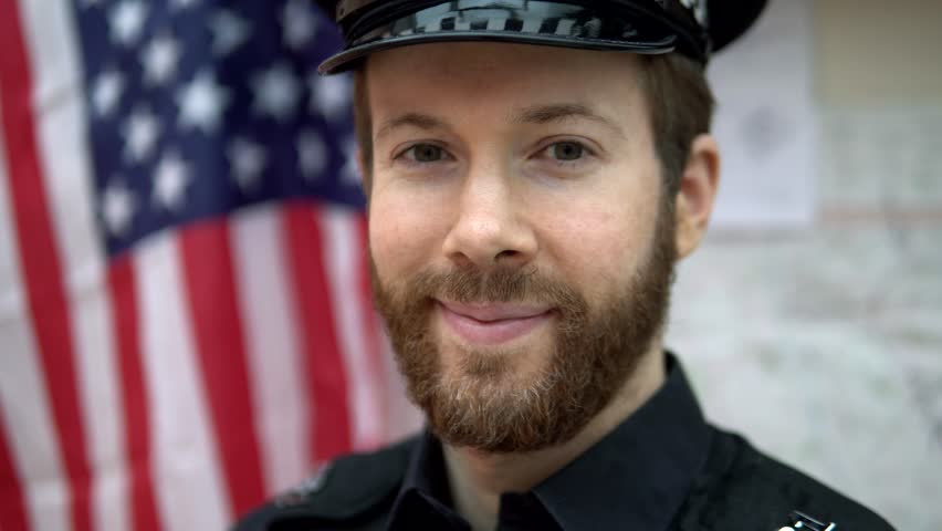 Portrait Of Brave American Cop, Happy Police Officer In Front Of US Flag 4K In Police Station.