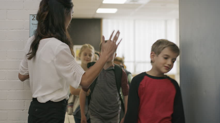 Enthusiastic teacher high-fiving students exiting doorway from classroom / Provo, Utah, United States #1008224179
