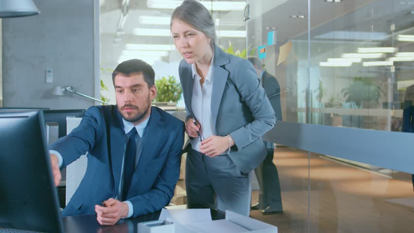 Business People Walking and Talking in the Hallway, Top Manager and Businesswoman Have Conversation in the Office, Use Desktop Computer. Corporate Office with Many Busy Workers. Shot on RED EPIC-W 8K