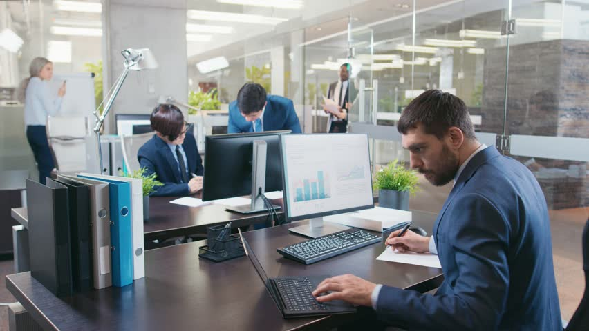 Professional Businessman Works on His Desktop Computer, Uses Laptop. In the Background Busy Office with Diverse Group of Business People. Modern Glass and Marble Corporate Building. 4K UHD.