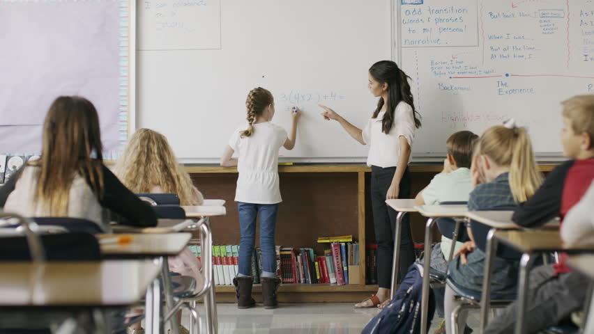 Teacher watching girl solving math equation on classroom whiteboard / Provo, Utah, United States #1008225601