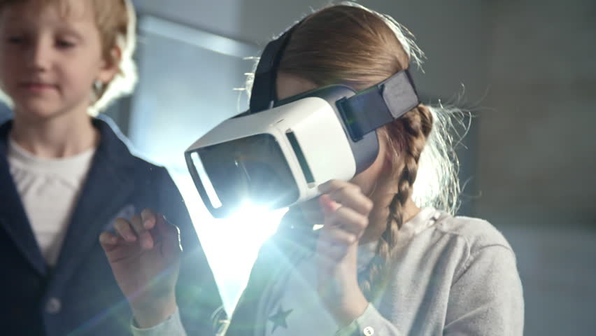 Primary school girl with two braids using virtual reality glasses as part of information technology lesson #1008227536