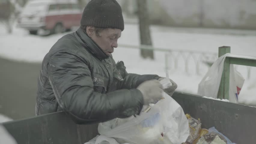Poverty: A beggar homeless man digs in a garbage can | Shutterstock HD Video #1008235291