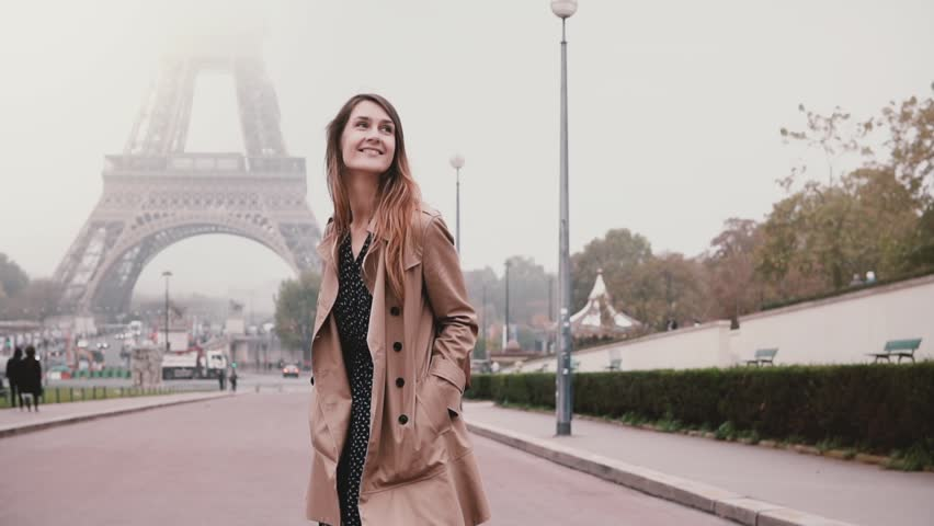 Young attractive woman walking near Eiffel tower in Paris, France. Happy girl looking around and smiling. Slow motion.