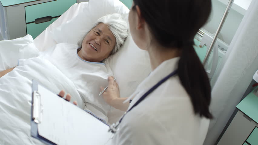 High angle shot of recovering senior woman lying in hospital bed and talking with caring female doctor making notes and supporting her