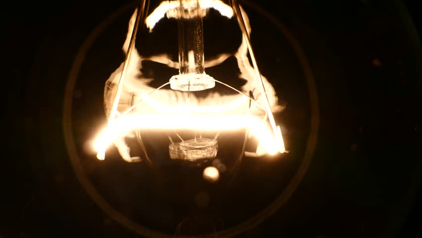 The incandescent lamp with a tungsten filament wobbles on the wire. The light flashes due to a poor contact. Electric power was lost in the room. Light from a light bulb. Bulb close-up. | Shutterstock HD Video #1008258316