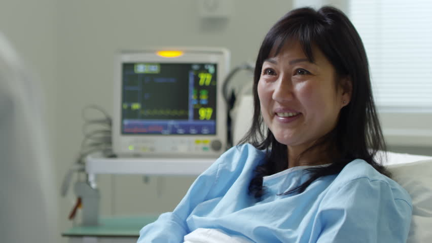 Tilt up of cheerful female patient in hospital gown chatting and shaking hands with unrecognizable doctor Royalty-Free Stock Footage #1008263395