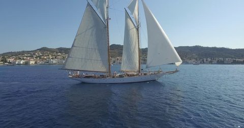 Cinematic drone shot of luxury yacht sailing near the island of Spetses