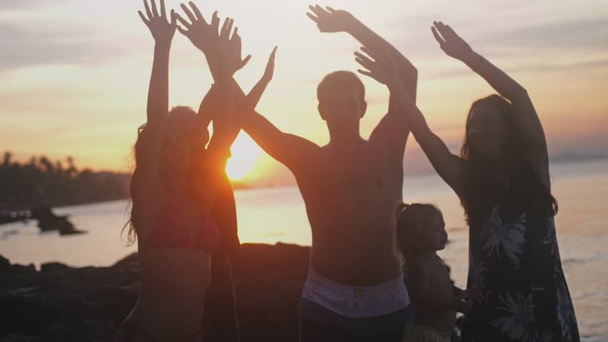 Happy young friends with children having fun singing song and dancing rising their hands on a tropical beach during sunset. slow motion. 3840x2160 #1008283552