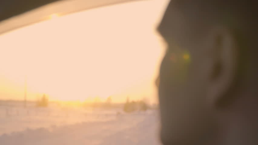 Young man riding in car looking around at sunset sunrise winter, changing focus | Shutterstock HD Video #1008284053