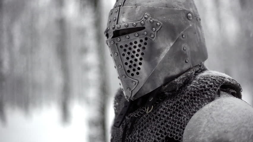 Portrait closeup of militant medieval knight wearing traditional steel armor and helmet, sword fighting in winter wood slow motion. Fantasy and reenactment