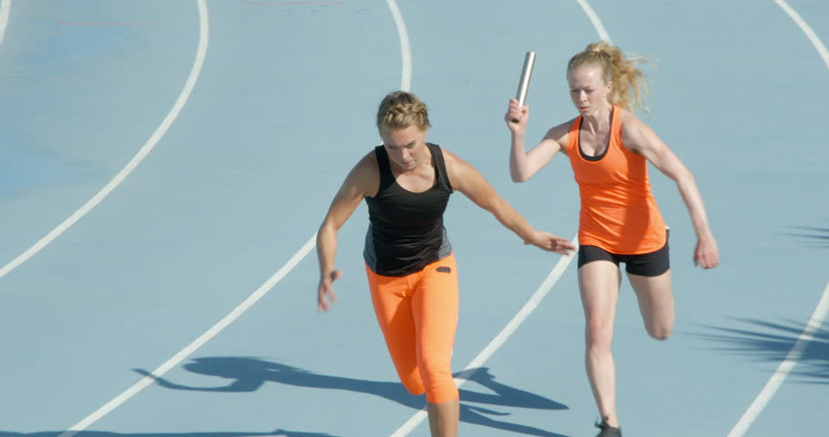 Two women running a relay race in slow motion pass the baton in slow motion.