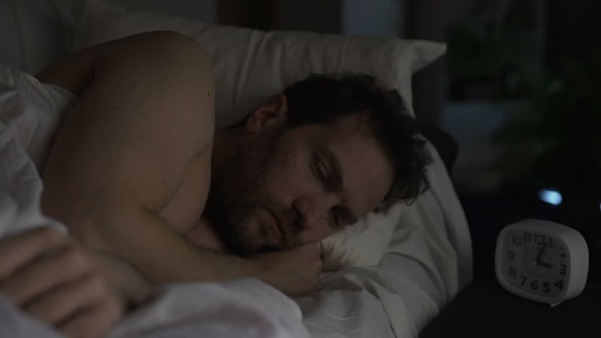 Guy turning in bed unable to fall asleep, looking angrily at clock, insomnia | Shutterstock HD Video #1008300181