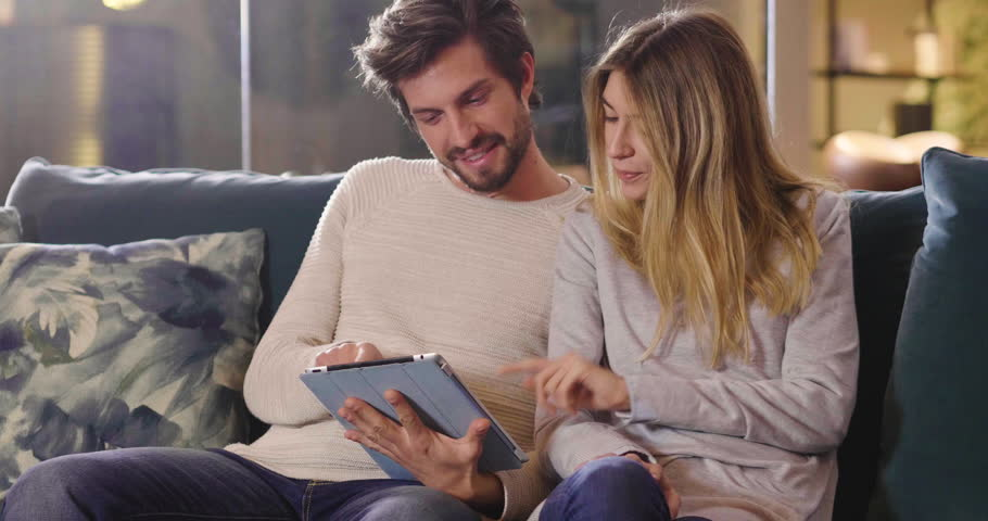 A couple in the kitchen looks at the tablet with the souvenir photos of their holidays or of the past times while having breakfast and smiling happily. Concept of: family, technology, memories. #1008301291