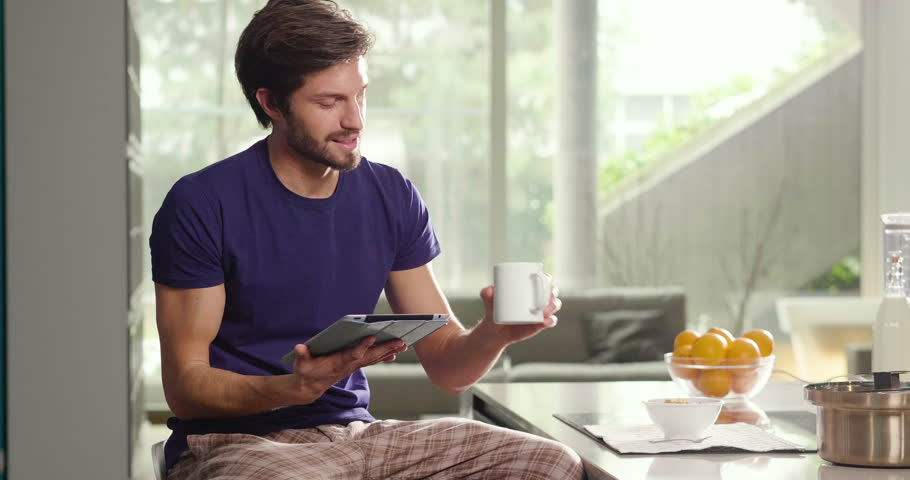A man in the kitchen while having breakfast and sipping tea or milk in the cup sends a message or calls with the tablet and smiles. Concept of: social network, message, technology.