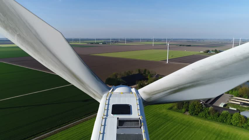 Aerial top down view wind turbine in polder landscape moving above the white modern construction of the wind turbine is device that converts winds kinetic energy into electrical energy 4k quality