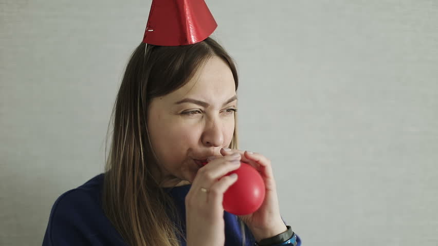 An adult woman in a festive hat inflates a red balloon indoors. Preparation for the holiday. Birthday. Slow motion. | Shutterstock HD Video #1008312694