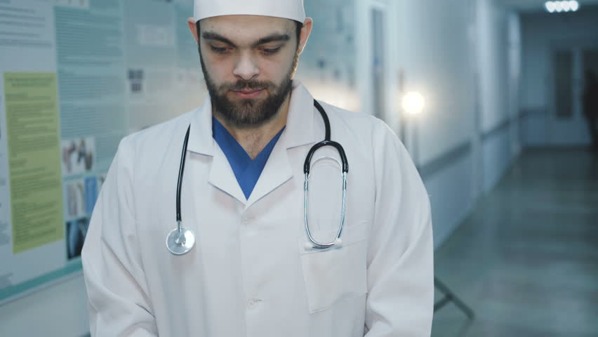 Portrait of handsome smiling doctor looks at camera in hospital. 4K. | Shutterstock HD Video #1008317731