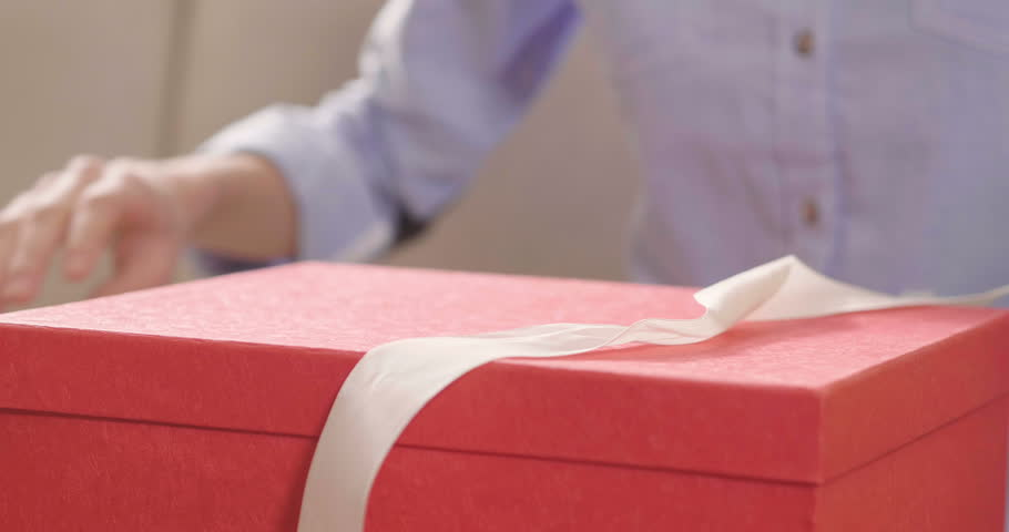Close up of an young woman is opening a gift box arrived at home ordered by using online shopping. Concept of shopping, love, gift, anniversary.