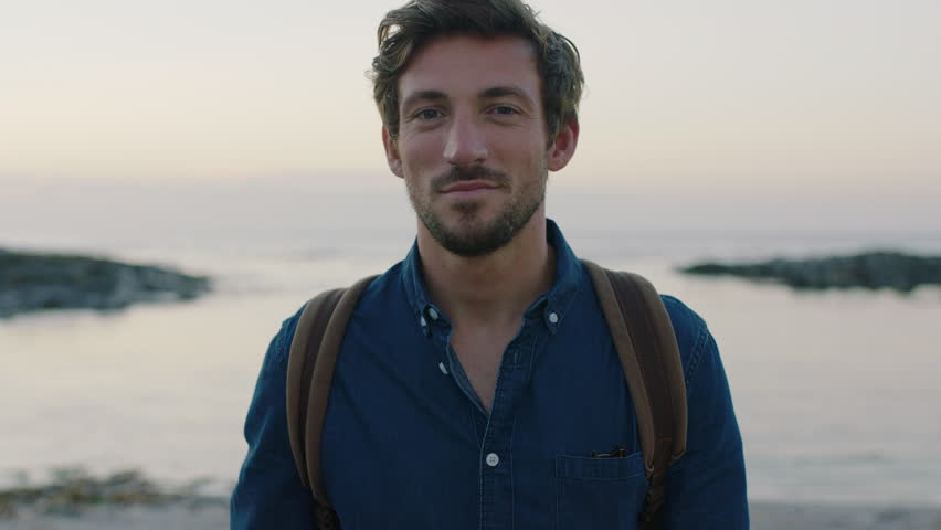 Portrait of attractive charming caucasian man smiling confident on calm seaside beach at sunset wearing blue shirt