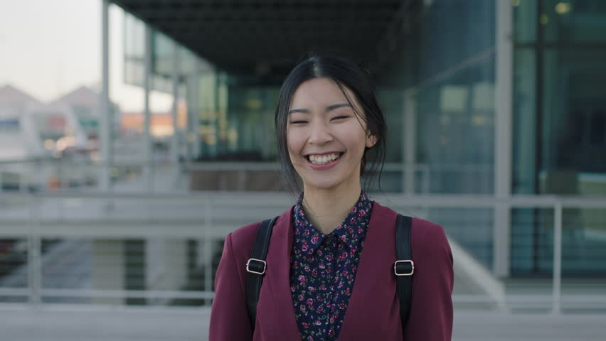portrait of young asian woman student laughing happy standing campus university learning #1008365467