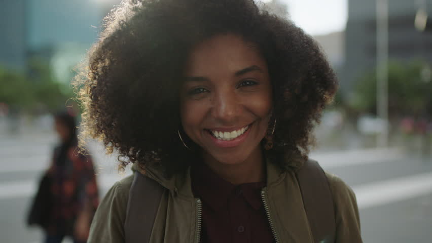 Portrait of beautiful trendy african american woman smiling at camera looking confident running hand through hair enjoying urban city lifestyle real people series