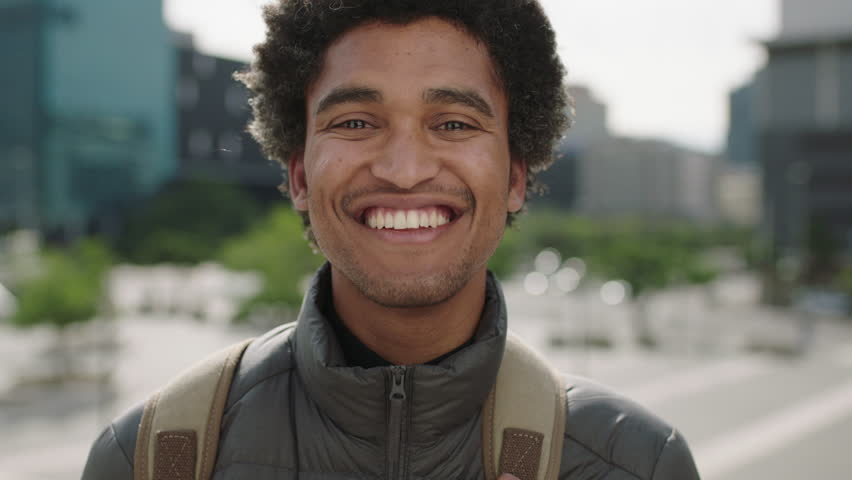 Portrait of handsome young mixed race man laughing cheerful at camera enjoying sunny urban city commuting travel lifestyle
