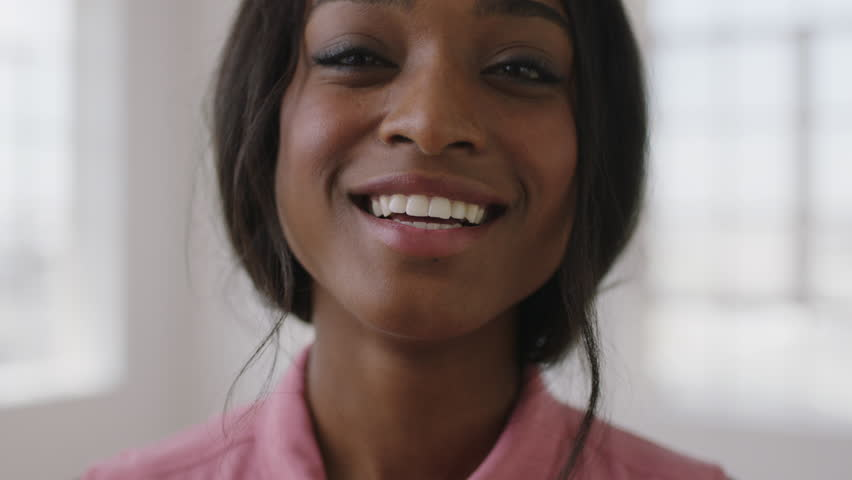Close up portrait of young pretty african american woman laughing happy enjoying positive lifestyle move in new apartment wearing pink blouse