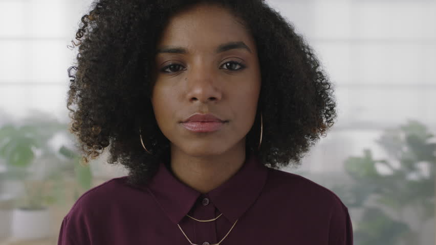 portrait of confident young black business woman intern looking serious at camera independent african american female in office workspace background slow motion #1008365647