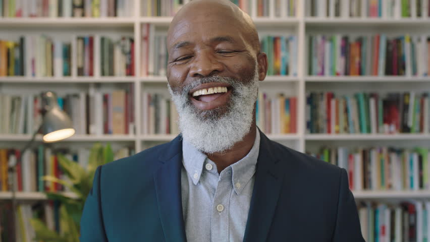 Close up portrait of mature african american businessman with beard laughing happy enjoying successful career milestone professional senior black male wearing suit in library | Shutterstock HD Video #1008367480