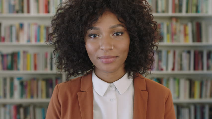 portrait of stylish young african american business woman intern laughing cheerful at camera in library bookshelf background real successful female entrepreneur